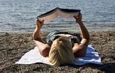Woman reading a book on the beach — Stock Photo