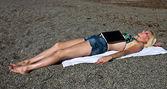 Mujer joven con un libro durmiendo en la playa — Foto de Stock
