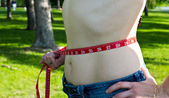 Fit young woman with measuring tape aroung waist — Stock Photo