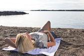 Mujer joven en la playa escuchando música — Foto de Stock