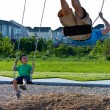 Child and father playing on the swing set — 图库照片