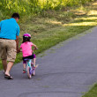 Child learning to ride bicycle with father — Stock Photo #30102261