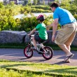 Child learning to ride a bicycle with father — Stock Photo