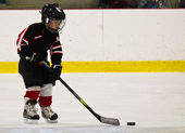 Child skating and playing hockey in an arena — Stock Photo