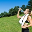 Athletic woman drinking water after a workout — Stock Photo