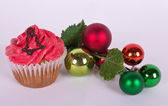 Christmas tree ornament and cupcake with bell — Stock Photo