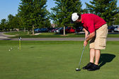 Golfer practicing putting golf balls — Stock Photo