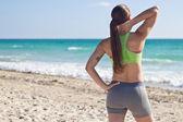 Přizpůsobit žena odpočívá po spuštění na pláži — Stock fotografie