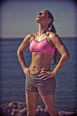 Fit woman worshiping the sun - contrast filter applied — Stock Photo