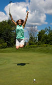 Woman jumping for joy as the golf ball heads into the cup — Stock Photo