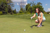 Woman lining up her putt on the golf green — Stock Photo