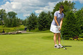 Female golfer putting the golf ball on the green — Stock Photo