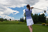 Female golfer swinging her golf club — Stock Photo