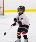 Child making a pass while playing ice hockey — Stock Photo