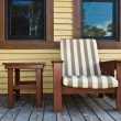 Chair on a wooden deck at a cottage — Stock Photo #49280301