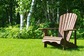 Wooden Adirondack summer lawn chair outside on the green grass — Stock Photo