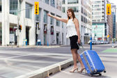 Traveling Business Woman Hails a Taxi on a city street — Stock Photo