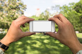 Man using mobile phone in the park as camera — Stock Photo