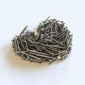 Corazón de metal clavos sobre un fondo blanco — Foto de Stock