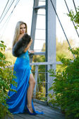 Beautiful blond girl standing on the bridge in the park. — Stock Photo