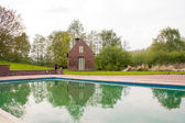 Old brick farm house with swimming pool — Stock Photo