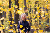 Young woman with falling autumn leaves — Stock Photo