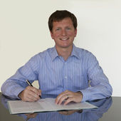 Signing document with blue shirt — Stockfoto