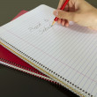 Teacher writing back to school in notebook — Stok fotoğraf
