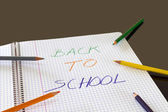 Back to school written in color on book, with colored pencils around — Stockfoto