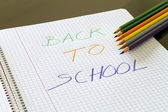 Back to school written in color on book, with colored pencils around in line — Stockfoto