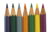 Seven colored pencils in a row — Stockfoto