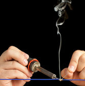 Technician soldering two wires together on a black background. — Stock Photo