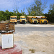 Old rusting fuel pump in front of yellow school buses in Governo — Stock Photo #17980923