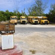 Stock Photo: Old rusting fuel pump in front of yellow school buses in Governo