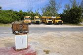 Antigua bomba de combustible aherrumbrar delante de autobuses escolares amarillos de governo — Foto de Stock