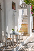 Table and chairs outside a typical house in Mykonos — Stock Photo