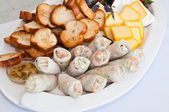 Springrolls, bread and cheeses — Stock Photo