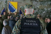 Bosnian Military officer protect a group of people — Stock Photo