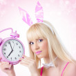 Pretty girl in bunny ears holding pink clock - Stock Photo