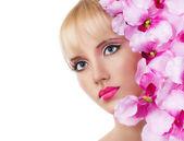 Mooi meisje met bloemen en roze make-up — Stockfoto