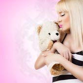 Beautiful young woman wearing pajamas embraces teddy bear — Stock Photo