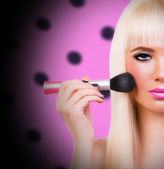 Blonde girl with make up brush — Stock Photo