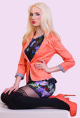 Beautiful fashionable blonde girl in orange jacket — Stock Photo