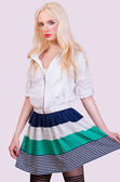 Beautiful fashionable blonde girl in skirt with stripes — Stock Photo