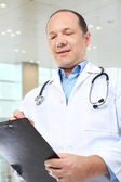 Medical doctor writing on clipboard — Stock Photo