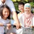 Happy muslim family riding bikes — Stock Photo