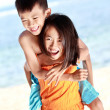 Stock Photo: Happy little girl carrying her brother