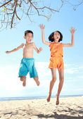 Jumping kids in the beach — Stock Photo