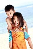 Mutlu küçük kız kardeşi taşıma — Stok fotoğraf