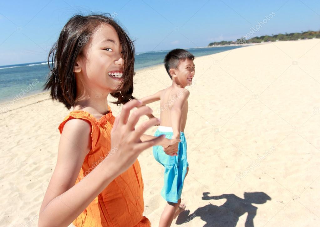 Portrait of happy little boy and girl running in the beach together  Stock Photo #12637470